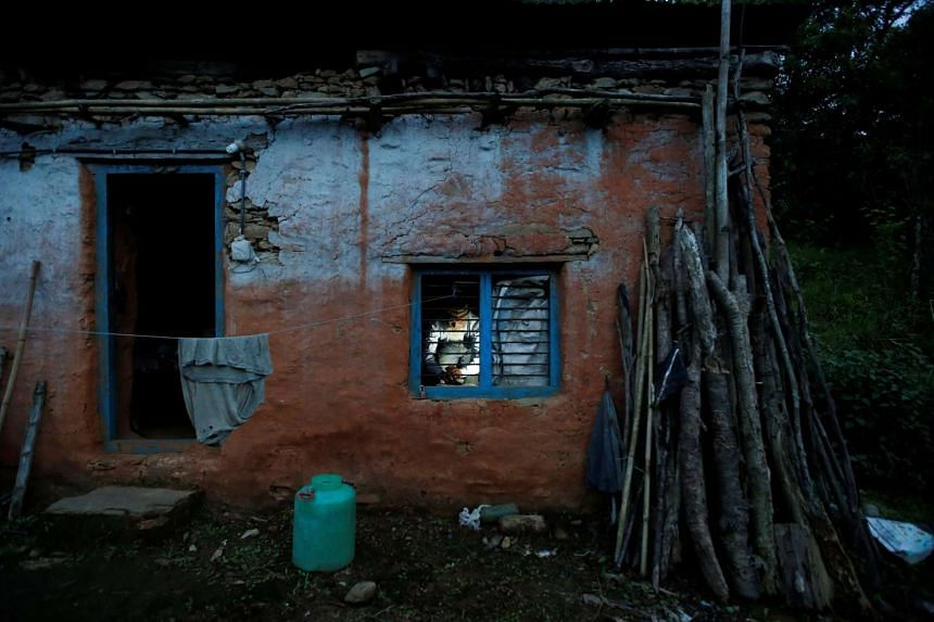 Durga Kami, 68, who is studying in the tenth grade at Shree Kala Bhairab Higher Secondary School, is seen through the window as he prepares dinner for himself at his one room house in Syangja, Nepal on June 4, 2016.