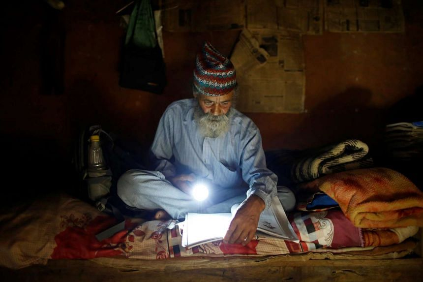 Durga Kami, 68, who is studying in the tenth grade at Shree Kala Bhairab Higher Secondary School, uses a torch to read a book during a power cut, at his one-room house in Syangja, Nepal, on June 4, 2016.