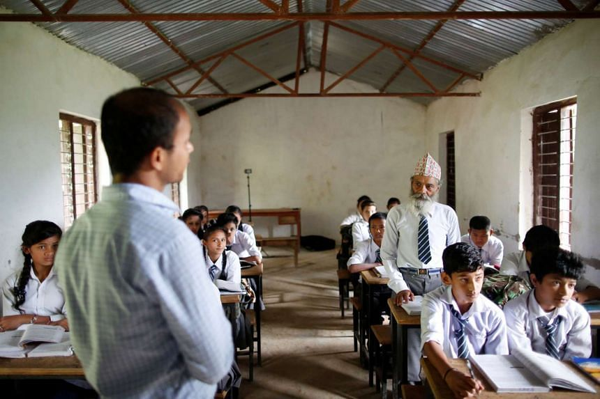 Durga Kami, 68, who is studying in tenth grade at Shree Kala Bhairab Higher Secondary School, answers a question from his teacher as he attends a class in Syangja, Nepal, on June 5, 2016.