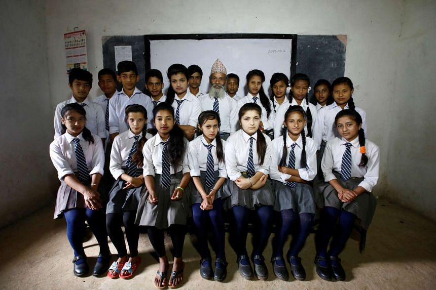 Durga Kami (centre), 68, and his classmates pose for a group picture in their classroom at Shree Kala Bhairab Higher Secondary School in Syangja, Nepal, on June 5, 2016.