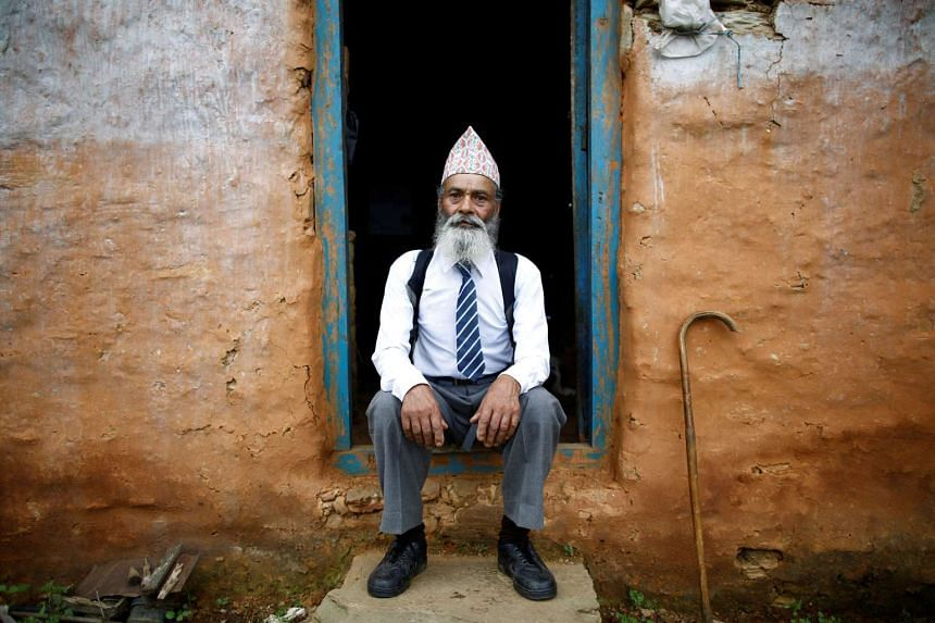 Durga Kami, 68, who is studying tenth grade at Shree Kala Bhairab Higher Secondary School, poses for a picture wearing his school uniform at the door of his one-room house in Syangja, Nepal on June 5, 2016.
