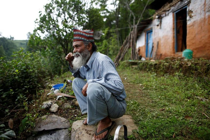Durga Kami, 68, who is currently studying tenth grade at Shree Kala Bhairab Higher Secondary School, brushes his teeth as he gets ready for school in Syangja, Nepal, on June 5, 2016.
