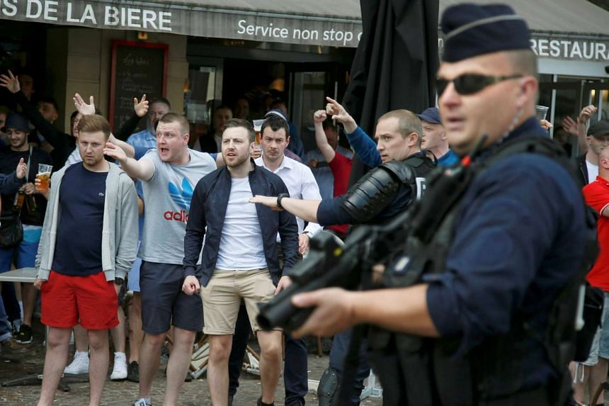 England and Wales fans react after some scuffles with Russian supporters outside a pub in Lille, France on June 14, 2016.