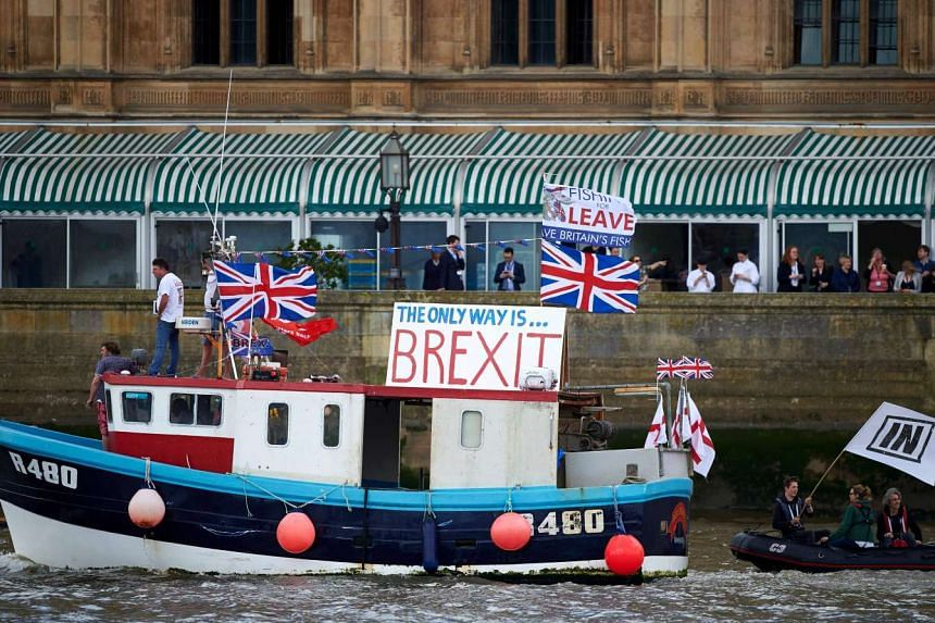 "A boat decorated with flags and banners from the ""Fishing for Leave""sails by the British Houses of Parliament as part of a ""Brexit flotilla"" on the river Thames in London on June 15, 2016."