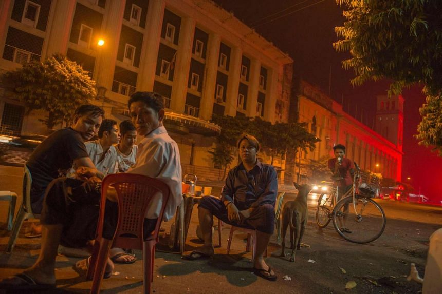 Office workers in Myanmar enjoying food and drinks along Yangon city's central Pansodan road.