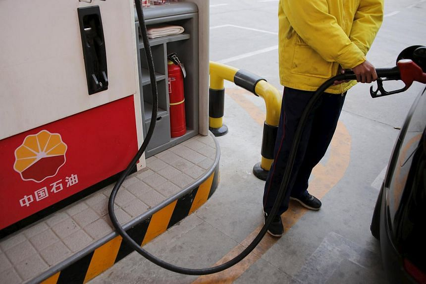 An attendant filling a customer's car at a PetroChina station in Beijing.