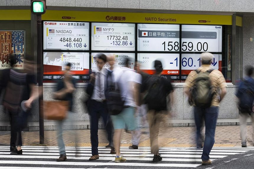 Pedestrians walking past an electronic stock board outside a securities firm in Tokyo on June 14.