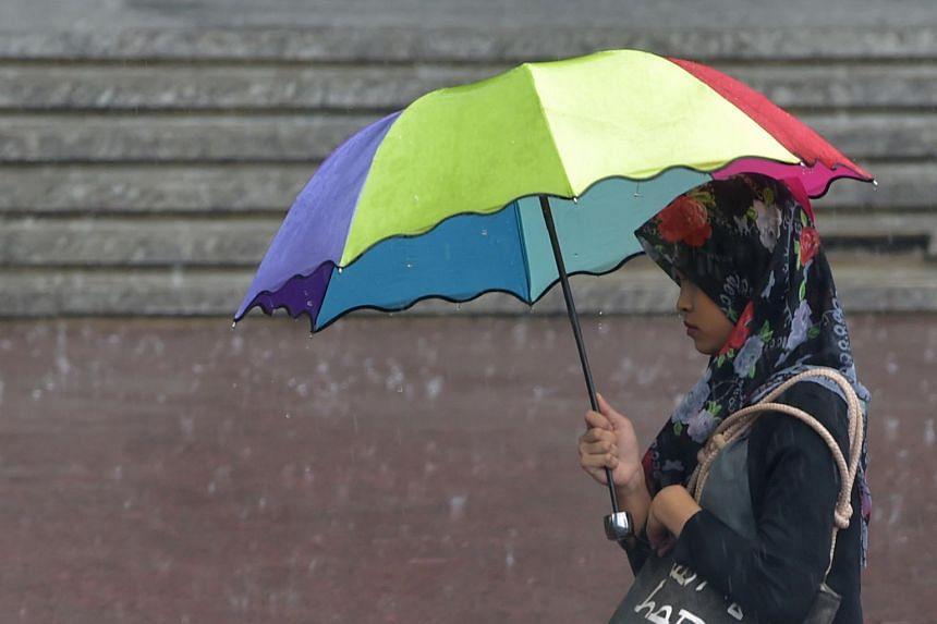 A woman walking in the rain in Jakarta on May 17.