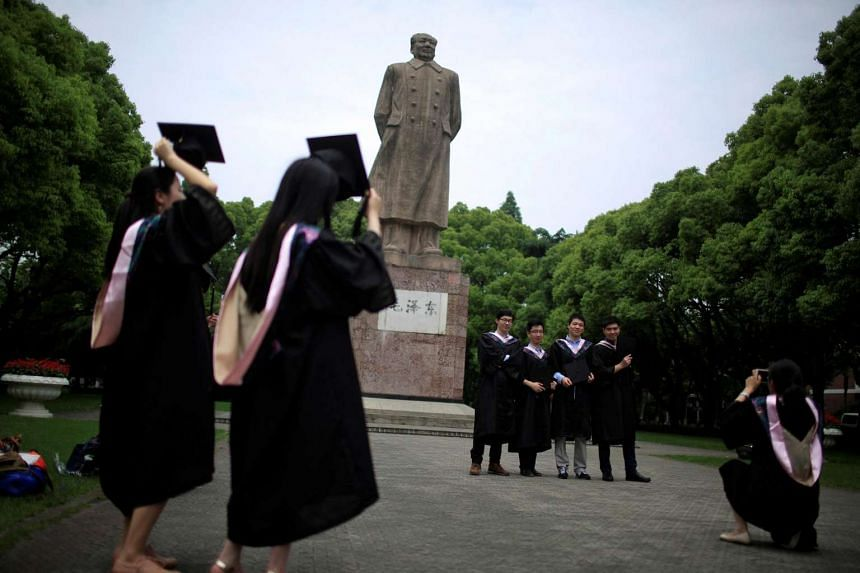 Graduates taking pictures in front of the statue of Chinese leader Mao Zedong at Fudan University in Shanghai.
