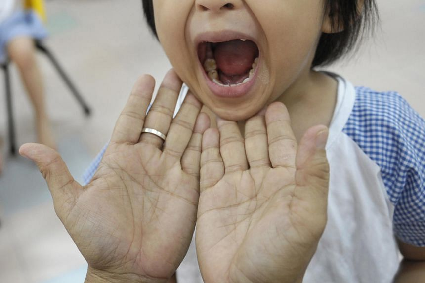 A child gets her mouth checked for hand, foot and mouth disease at a kindergarten.