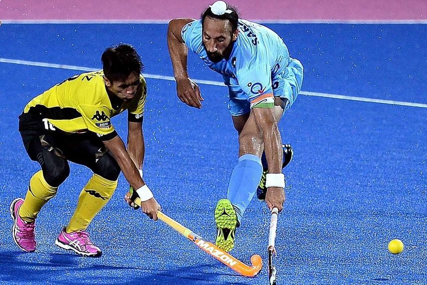 India's Sardar Singh (right) fights for the ball with Faiz Jali of Malaysia during their match of the 2016 Sultan Azlan Shah men's field hockey tournament, on April 15, 2016.
