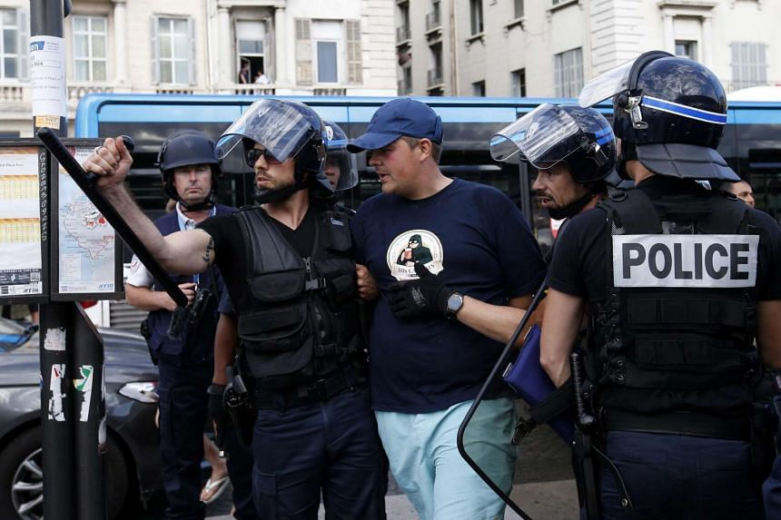 Riot police officers arrest a man after clashes bewteen English and Russian supporters at the Old Port of Marseille, France, on June 10, 2016.