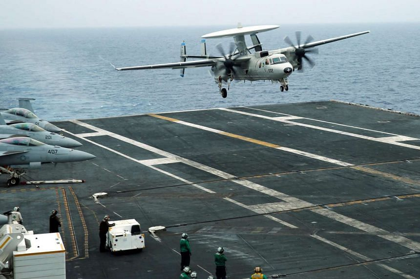 An E-2D Hawkeye plane approaches  the US aircraft carrier John C. Stennis during a joint military exercise, with the United States, Japan and India participating, off Okinawa, Japan on June 15, 2016.