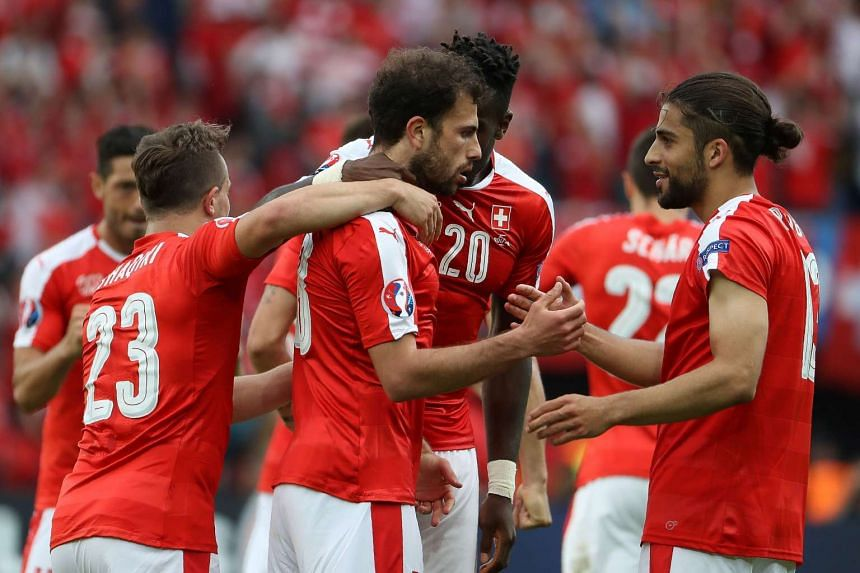 Switzerland's forward Admir Mehmedi (centre) celebrates with team mates after scoring.