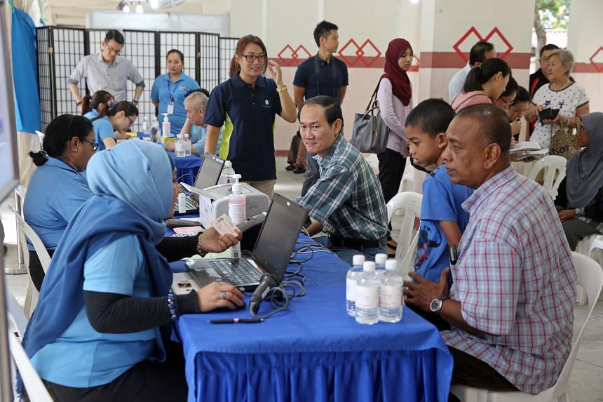 Residents from Block 203, Ang Mo Kio Avenue 3, undergo health screening at the void deck on Thursday (June 16).