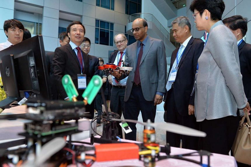 Director of Delta-NTU Corp Lab Prof Xie Lihua (second from left) speaking to Deputy Prime Minister Tharman Shanmugaratnam on the latest innovation.