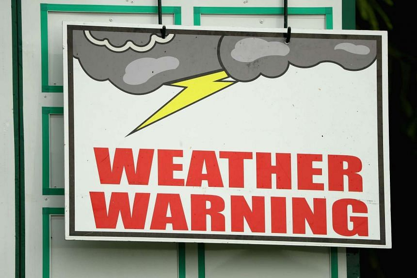 A weather warning sign on a leaderboard during the first round of the US Open at Oakmont Country Club.
