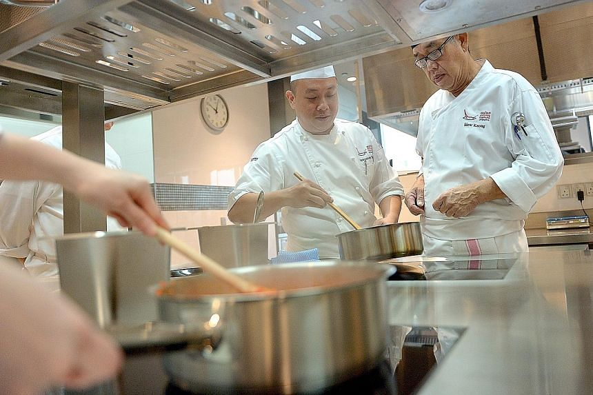 Trainer Lawrence Toon (left), 41, guiding a trainee in the WSQ Certificate in Asian Pastry and Bakery class, where trainees are taught baking techniques, mixing methods and piping skills.