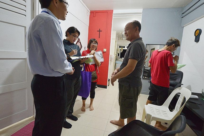 Residents' committee members and Health Ministry officials visiting Mr Bu Qing Liang (in grey), 48, at his home in Block 203, Ang Mo Kio Avenue 3, yesterday. All residents of the block are being urged to go for a free TB screening that will be provid