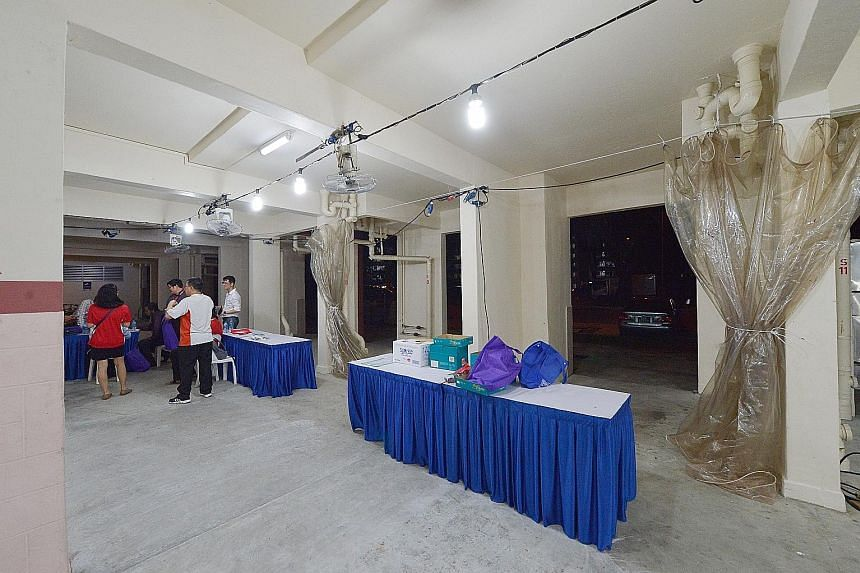 Mobile TB screening stations being set up at the void deck of Block 203, Ang Mo Kio Avenue 3, last night. MOH is providing voluntary free screening for residents from today until Sunday as a precautionary measure, to pick up any undiagnosed or latent
