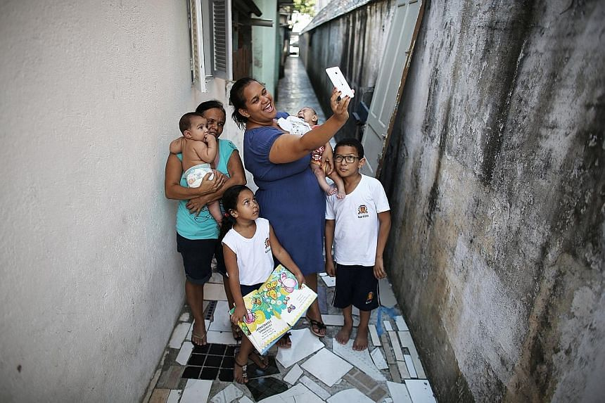 Brazilian mother Jaqueline Jessica Silva de Oliveira taking a selfie with her family in April. She recently gave birth to twins, and one of them has microcephaly, a birth defect associated with Zika.