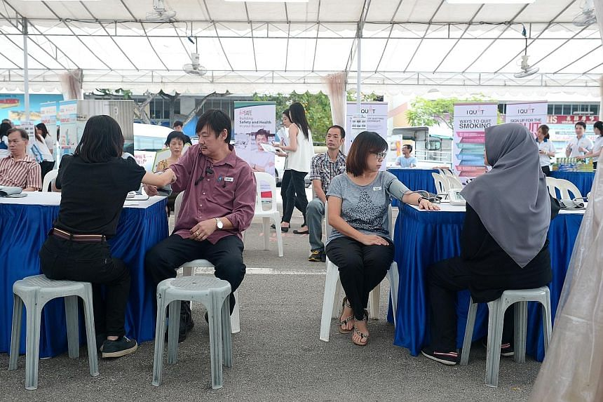 Workers taking advantage of a free medical check-up in a pop-up tent at Tampines Industrial Park A, organised by HPB as part of the Healthy Workplace Ecosystem initiative.