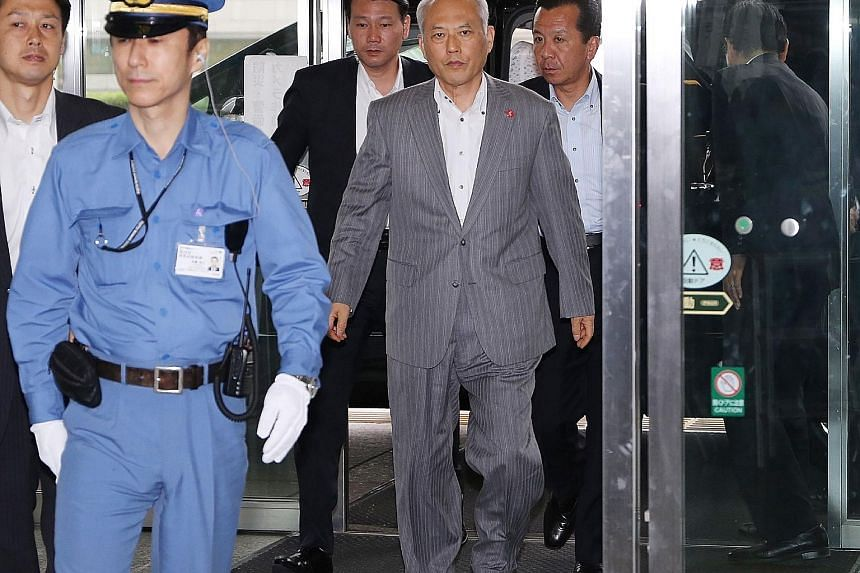 Mr Masuzoe (in grey suit) has been under fire over misuse of tax money on personal expenses, including family trips.