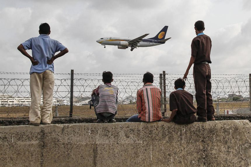 People watch as a Jet Airways (India) Ltd. aircraft prepares to land at Chhatrapati Shivaji International Airport in Mumbai, India, on May 23, 2013.