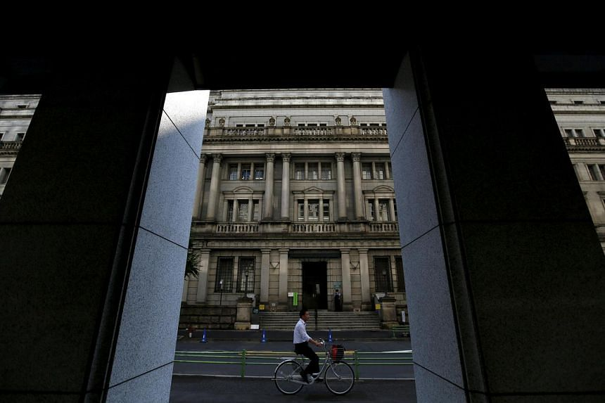 A man cycles in front of the Bank of Japan building in Tokyo, in 2015.