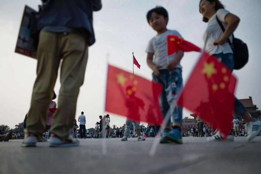 A child stands next to national flags in Tiananmen Square in Beijing on June 4.