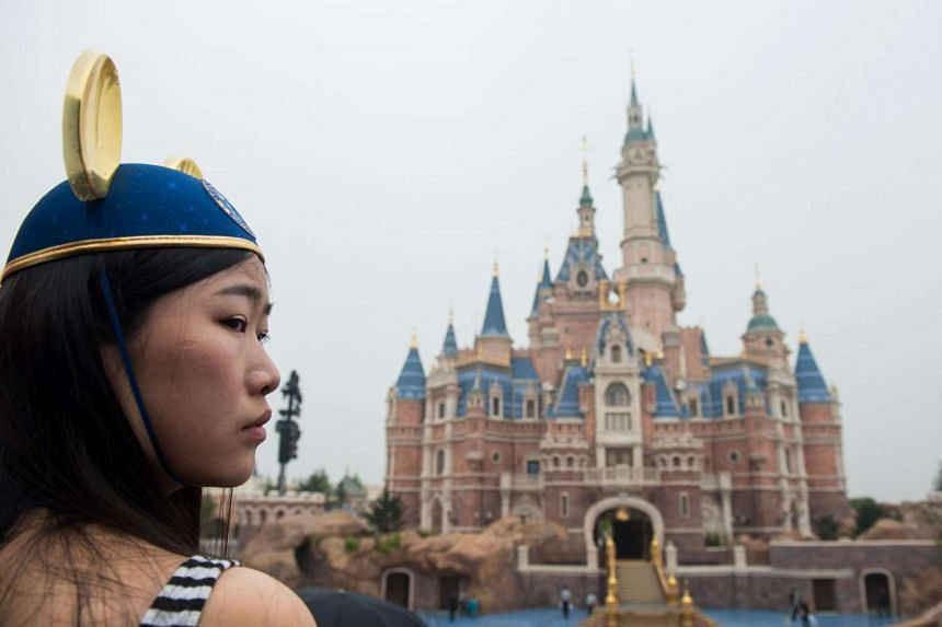 A girl wearing Mickey Mouse ears watching the opening ceremony of the Shanghai Disney Resort on June 16.