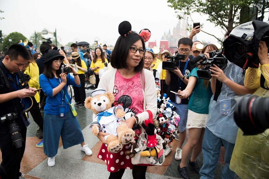 A visitor holding a bag with stuffed animal toys on the opening day of the Shanghai Disney Resort on June 16.