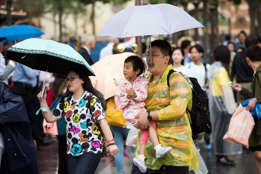 Visitors attend the opening day of the Shanghai Disney Resort in Shanghai on June 16.