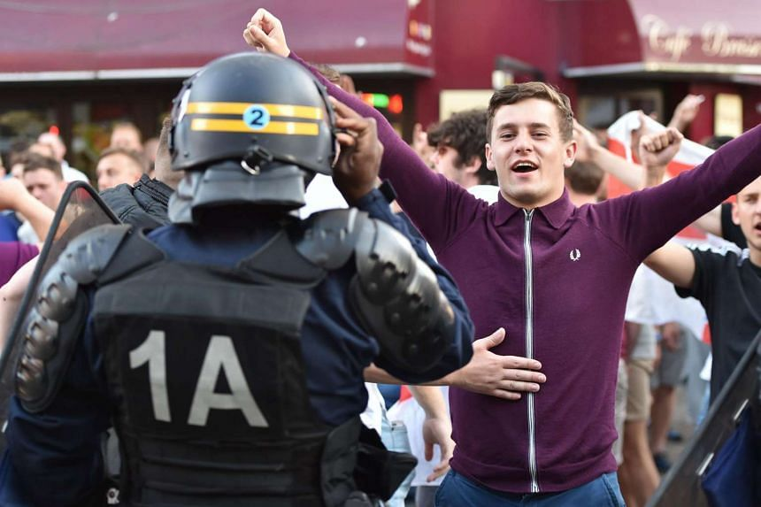 A French riot police officer talks to a football supporter in central Lille on June 15 during the Euro 2016 football championship.