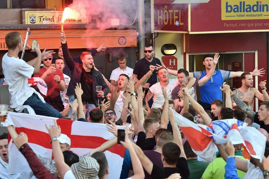 England supporters wave flags and light a flare in central Lille on June 15, 2016, on the sideline of the Euro 2016 football championship.