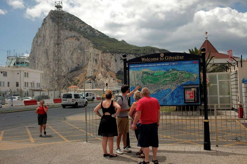British tourists look at a map in front of the Rock of Gibraltar (rear) before the arrival of British Prime Minister David Cameron.