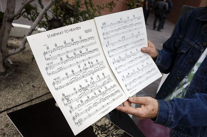 A Led Zeppelin fan holds up sheet music for Stairway to Heaven outside of federal court in Los Angeles, California, US on June 14.