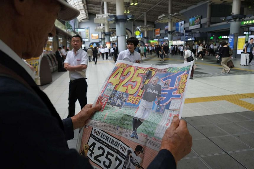 A man reads an extra edition of a local Japanese sports newspaper reporting on Major League Baseball player Ichiro Suzuki's record setting hits at a railway station in Tokyo on June 16, 2016.