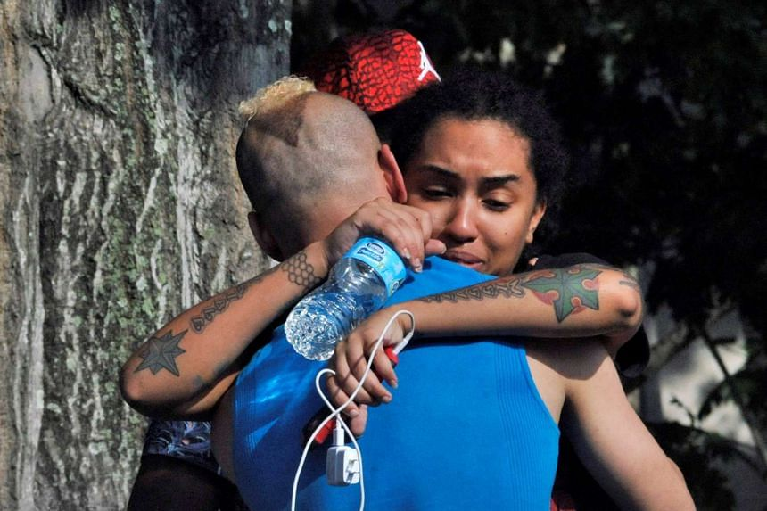 Friends and family members embrace outside the Orlando Police Headquarters during the investigation of a shooting at the Pulse nightclub.