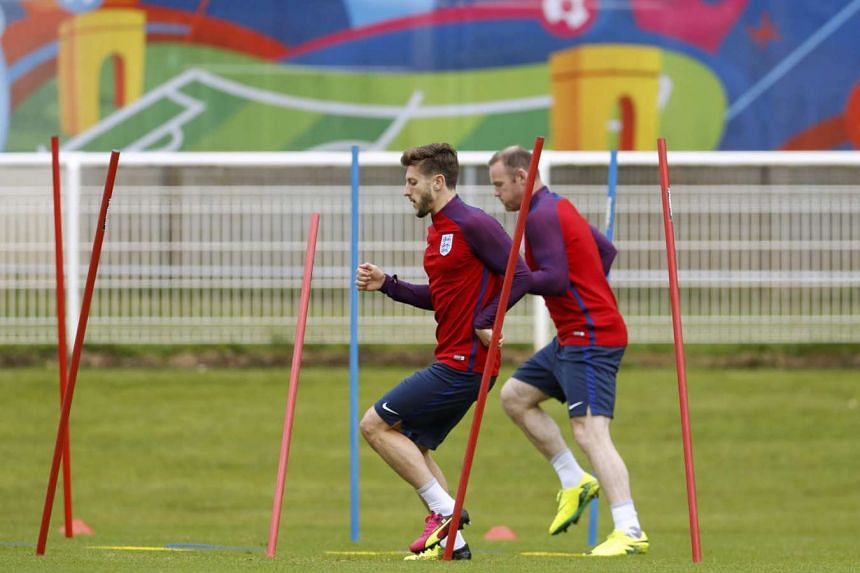 """England's Adam Lallana (left) and Wayne Rooney during a training session at Stade des Bourgognes in Chantilly yesterday. Lallana has said that elimination due to fan violence would be """"devastating"""", while captain Rooney and manager Roy Hodgson have appeal"""