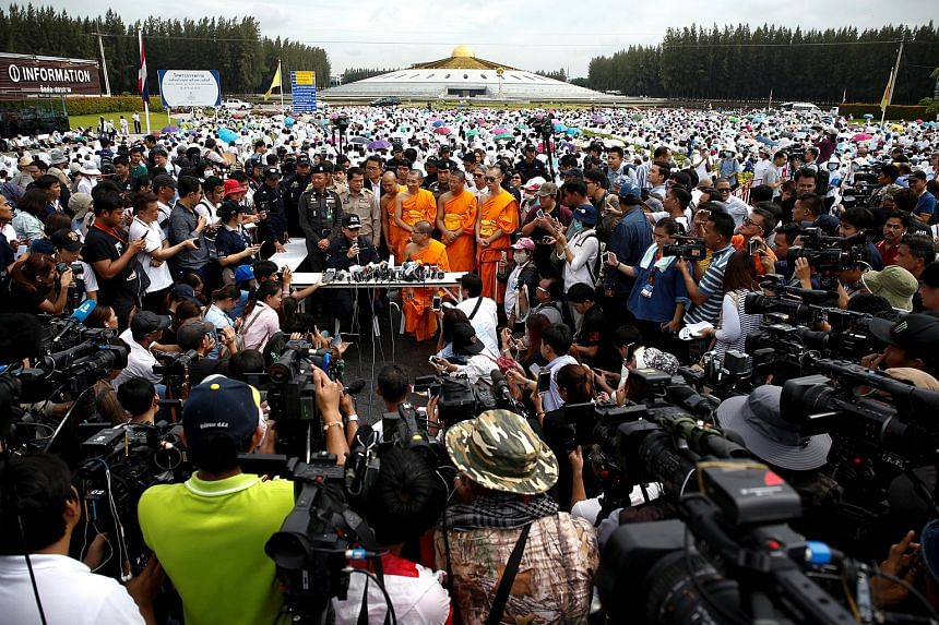 Thai police officers and Buddhist monks speak to the media inside the Wat Phra Dhammakaya temple complex before a planned police raid, in Pathum Thani province, north of Bangkok, Thailand, on June 16.