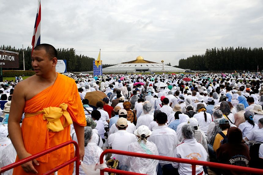 A buddhist monk and followers gather inside the Wat Phra Dhammakaya temple complex in anticipation of a planned police raid, in Pathum Thani province, north of Bangkok, Thailand, on June 16.
