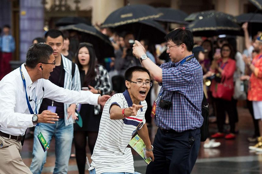 The first visitor reacts as he enters the Shanghai Disney Resort after the opening ceremony of the Shanghai Disney Resort in Shanghai on June 16.