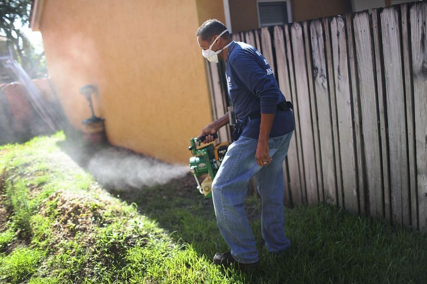 A mosquito control inspector uses a fogger to spray pesticide to kill mosquitoes on May 26, 2016, in Miami, Florida.