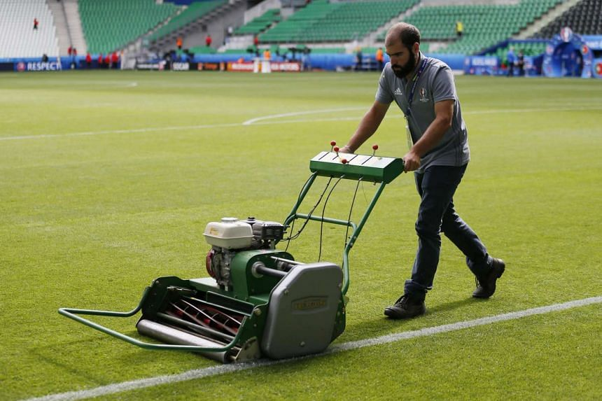 Ground staff work on the pitch before the Euro 2016 football match between Portugal and Iceland on June 14, 2016.