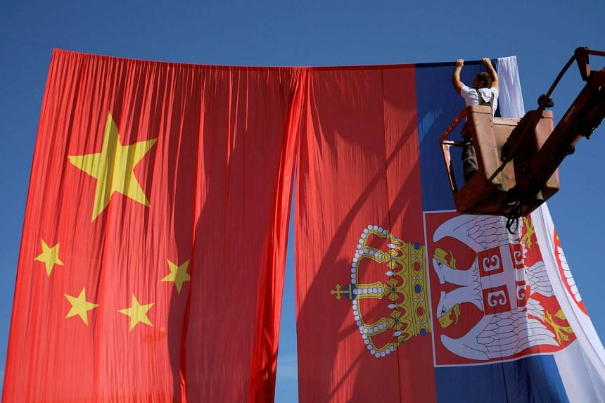 A worker adjusts Chinese and Serbian flags for the upcoming visit of Chinese President Xi Jinping, in Belgrade, Serbia, on June 16, 2016.