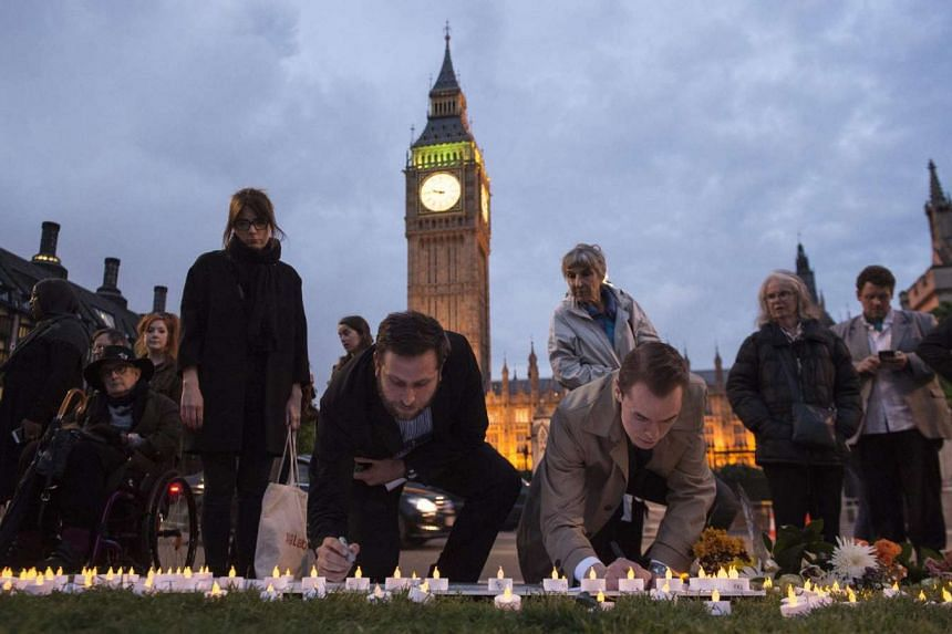 Members of the public sign a memorial to British MP Jo Cox in Parliament Square, London, on June 16, 2016.