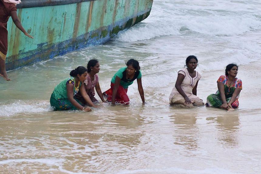 Migrant women from Sri Lanka jumping out from their stranded boat onto the beach in Lhoknga, Aceh province, on June 16, 2016.