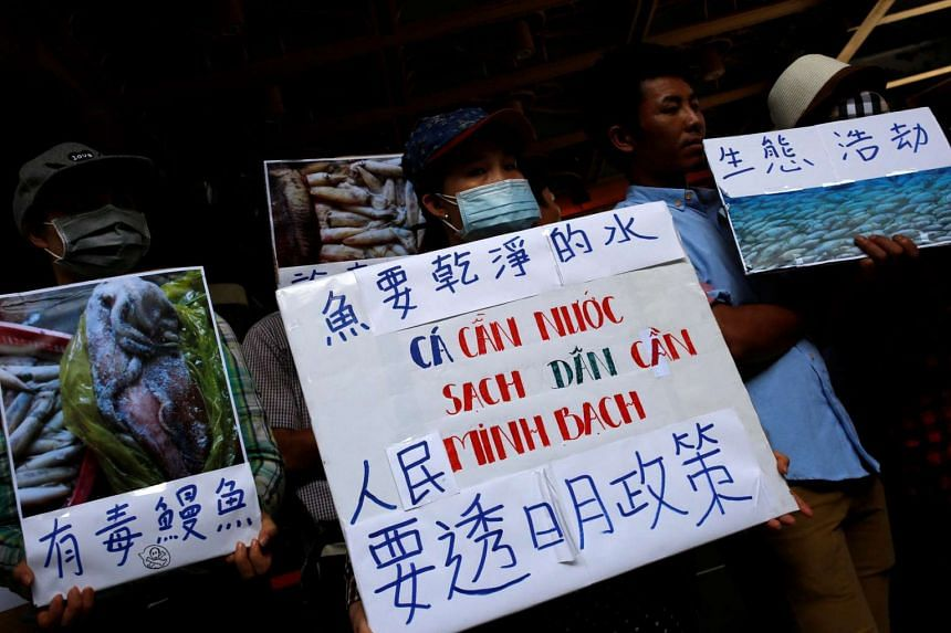 Protesters hold placards calling for Formosa Plastics to investigate and voluntarily disclose its findings on recent mass fish deaths in Vietnam, in Taipei, on June 17, 2016.