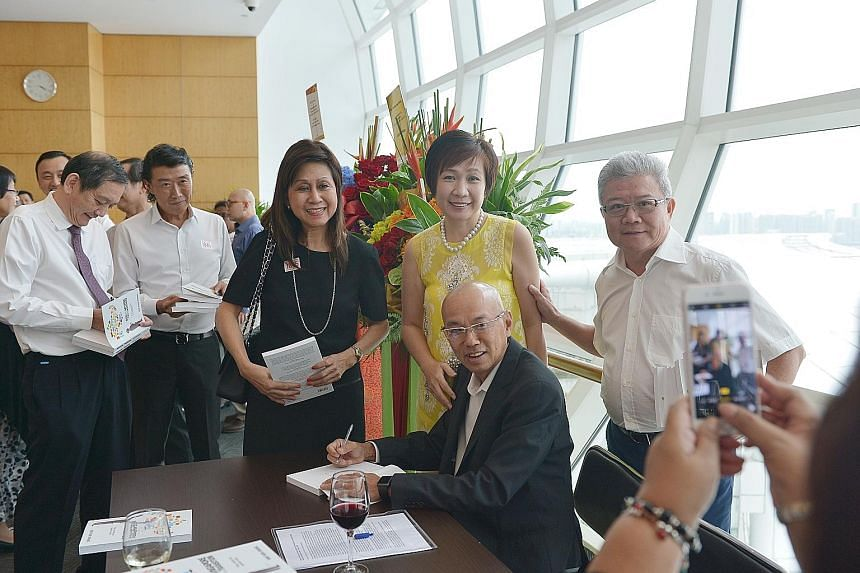 Guests with Mr Han (seated) at his book launch yesterday, including Mr Liak Teng Lit (at left), group CEO of Alexandra Health System.
